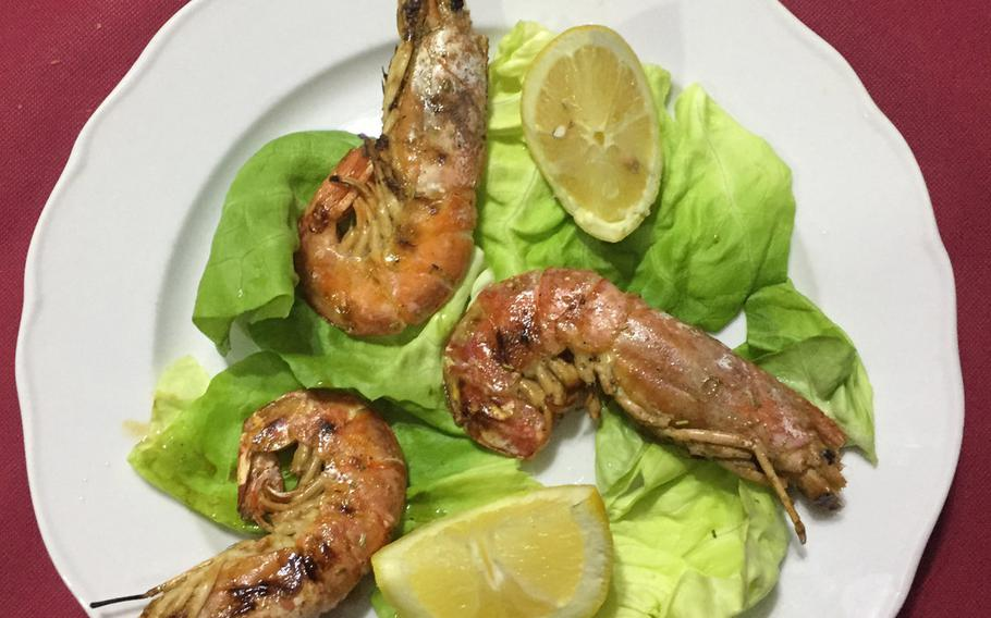 A trio of jumbo shrimp is one of many seafood choices at Ristorante Pizzeria Il Pentolone in the Parco Azzurro apartment complex in Pozzuoli, Italy.