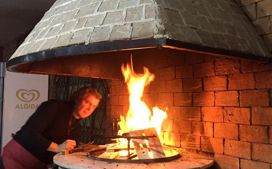 The owner of Ristorante Pizzeria Il Pentolone lights a fire to start the evening. You can choose from a variety of pizza, seafood and meat dishes at his restaurant located inside the Parco Azzurro apartment complex in Pozzuoli, Italy.