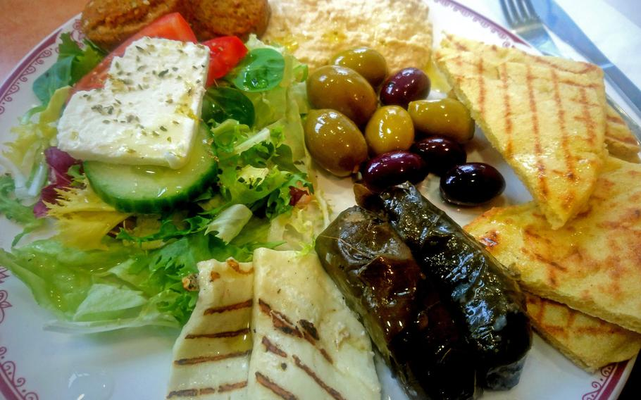 A Meze plate with grilled halloumi, mixed olives, hummus, falafels, stuffed vine leaves and salad with feta cheese at Cafe Kottani in Bury St Edmunds, England. There are four Meze plates for either 7.95 or 8.95 pounds ($11.25 to $12.66).