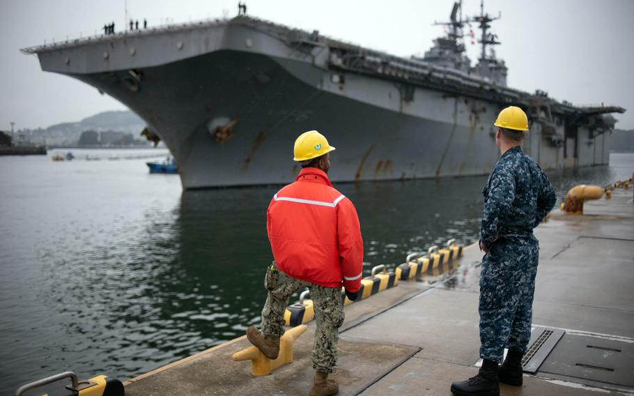 Sailors watch the USS Bonhomme Richard at Sasebo Naval Base, Japan, Tuesday, April 17, 2018.