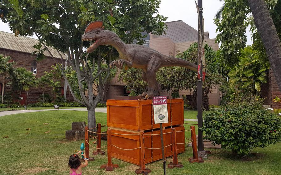 A prehistoric creature keeps watch outside the entrance to Expedition: Dinosaur at the Bishop Museum in Honolulu.