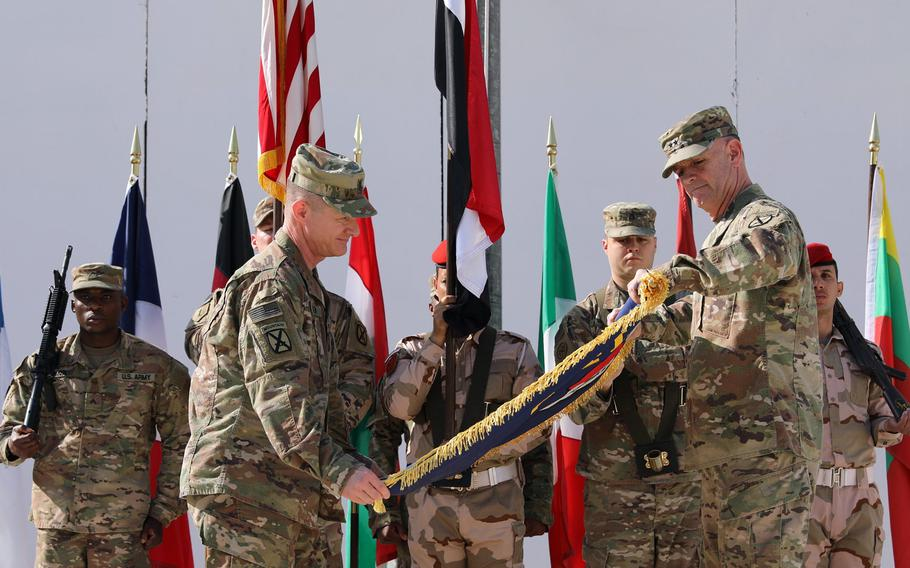Maj. Gen. Walter Piatt, right, commander of Combined Joint Forces Land Component Command, and his senior enlisted advisor, Command Sgt. Maj. Samuel Roark,roll up the CJFLCC flag during a deactivation ceremony in Baghdad, Iraq, April 30, 2018.
