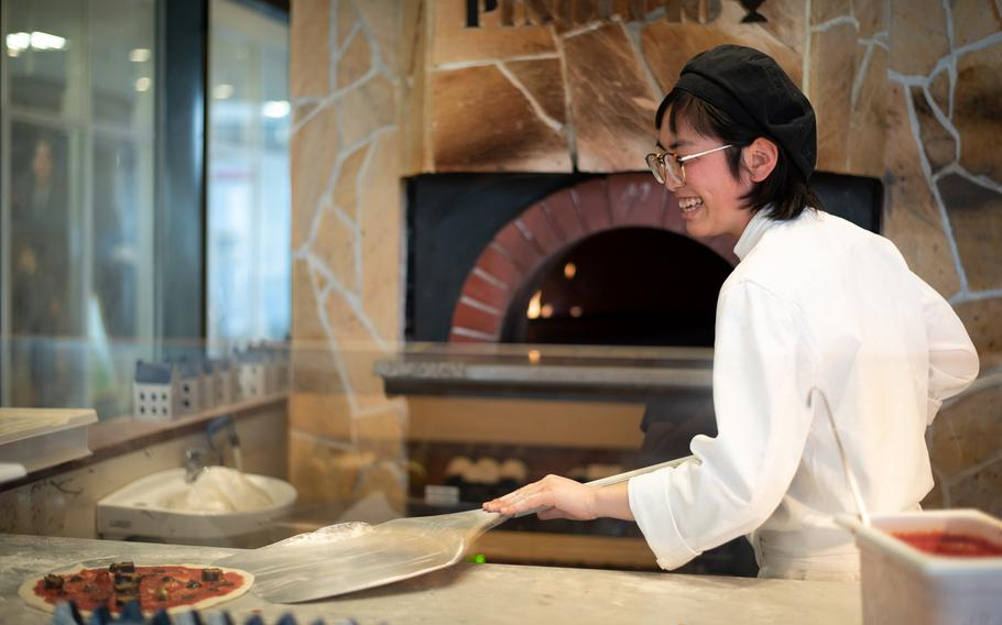 Maruolina, a chef at Pinoccio in Sasebo, gets ready to place a customer's pizza into the oven. The restaurant features an open kitchen, allowing diners to watch as their pizza is prepared.