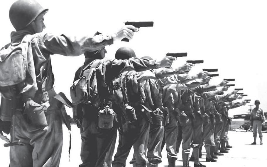 World War II troops on the firing line with their .45 caliber pistols.