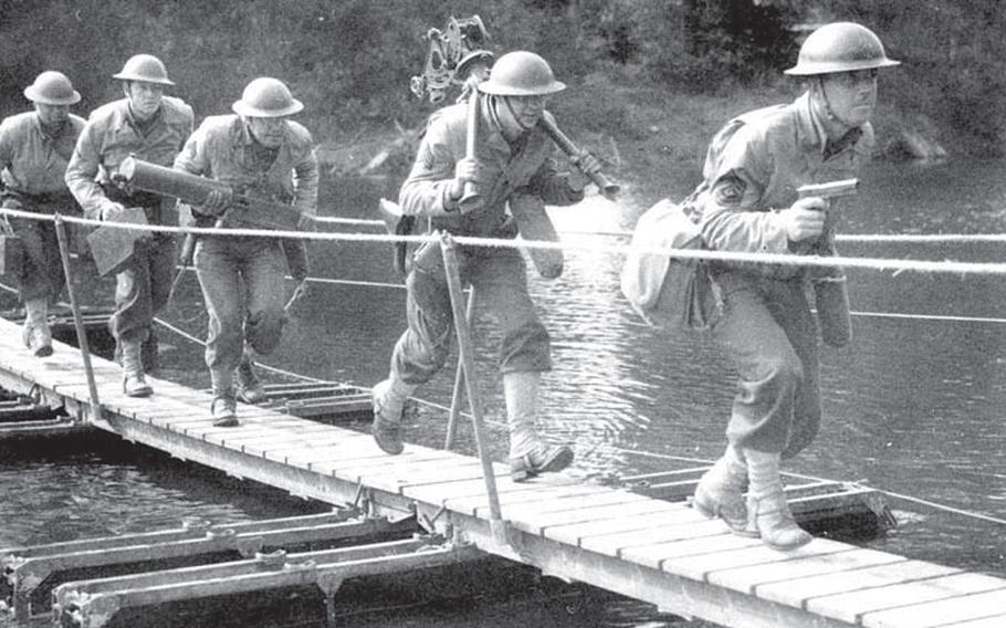 Led by their sergeant with his M1911 in hand, a .30-caliber machine gun team crosses a bridge during maneuvers in August 1941.