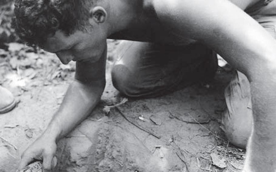"""In January 1967, a """"tunnel rat"""" from the 25th Infantry Division prepares to check a Viet Cong tunnel with his 1911 pistol and a flashlight."""