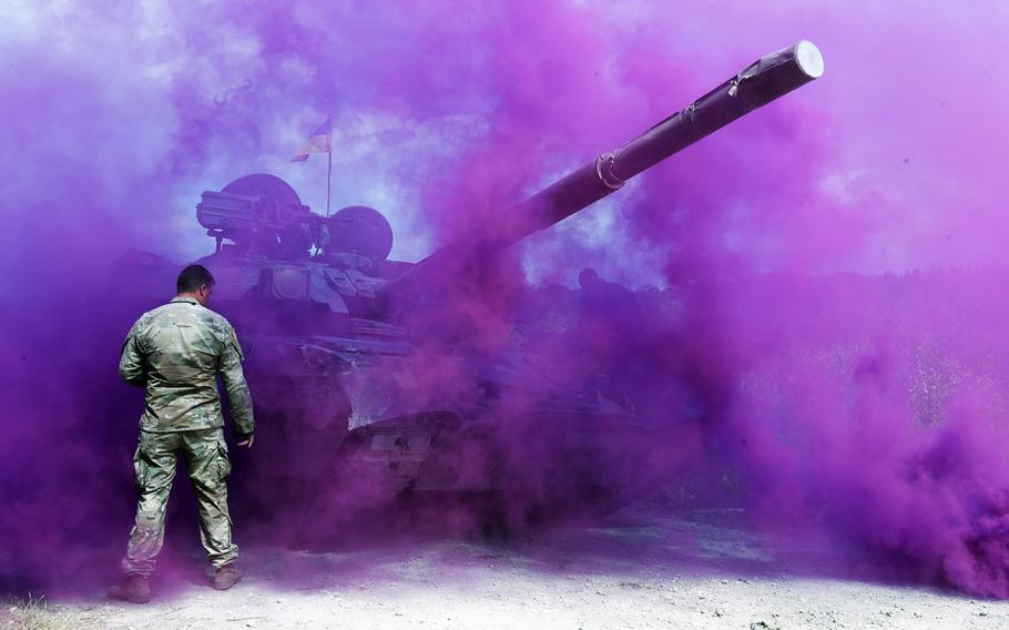 A U.S. soldier walks towards a Ukrainian T-84 tank through a cloud of smoke during the Strong Europe Tank Challenge in Grafenwoehr, Germany, Friday, June 8, 2018.