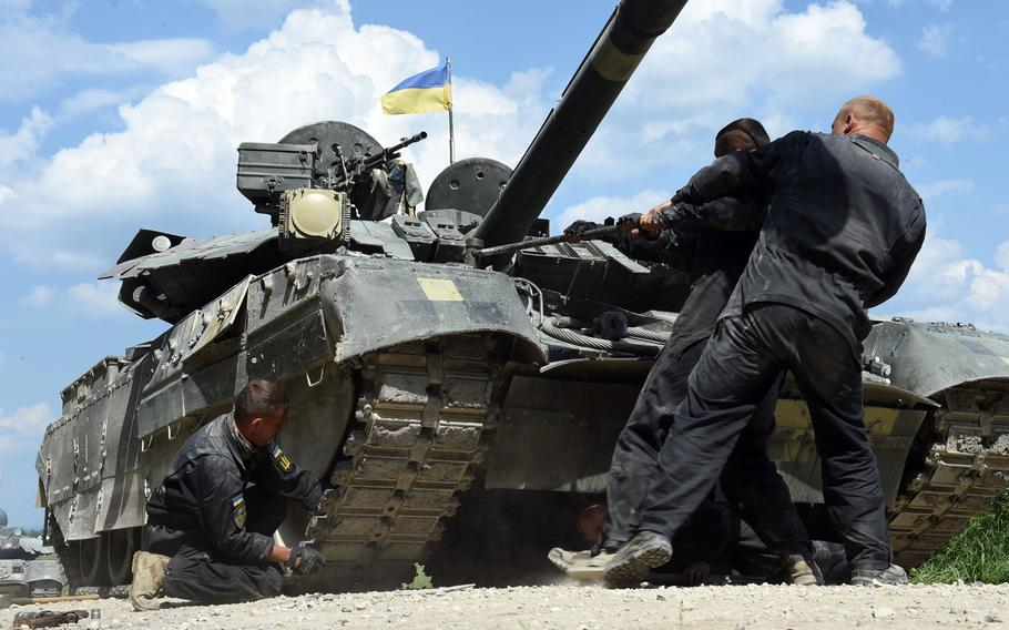 Ukrainian tankers fix their T084 tank after a mock improvised explosive device attack during the Strong Europe Tank Challenge in Grafenwoehr, Germany, Friday, June 8, 2018.