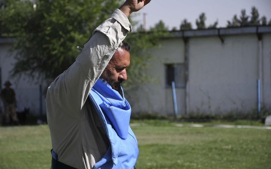 """Sahd Qasem, an Afghan de-miner, holds up his hand and yells """"Mine!"""" three times to indicate confirmation of explosive ordnance during training at the Mine Detection Center in Kabul, Afghanistan."""