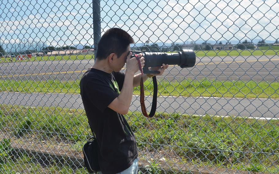 Military aircraft enthusiast Terutsugu Yamaguchi, 46, from Tokyo, photographs F-22 Raptor stealth fighters through the fence at Yokota Air Base, Japan, on July 9, 2018.