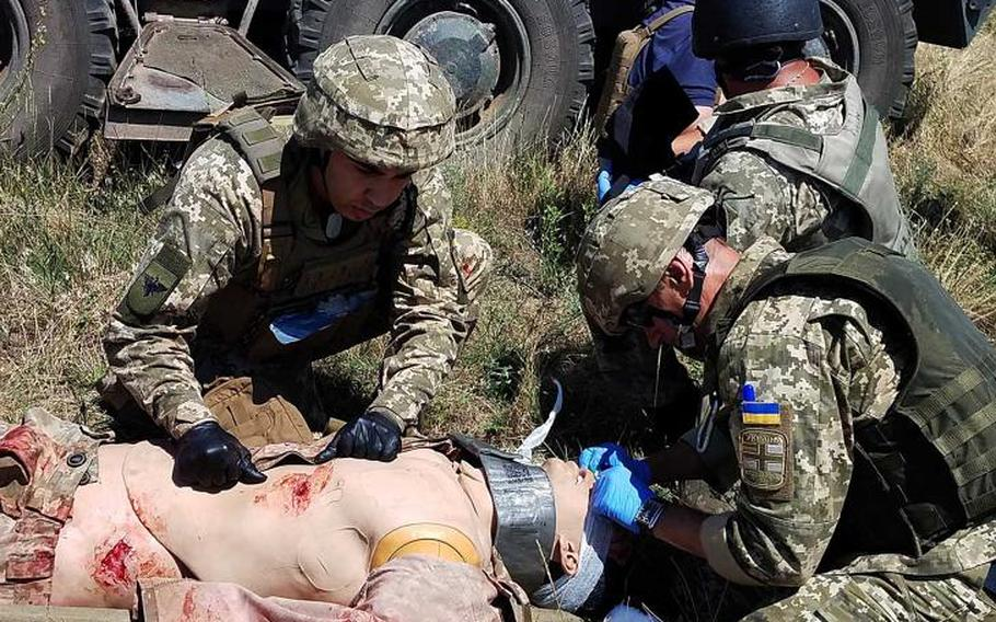 Ukrainian marines and officer candidates tend to a mock casualty during a live-fire exercise at the land portion of Exercise Sea Breeze, Saturday, July 14, 2018.