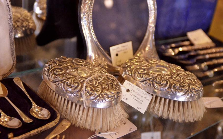 Silver brushes and dinnerware for sale at the Risby Barn Antique Centre in the village of Risby, England.