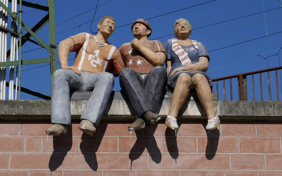 Three 1. FC Kaiserslautern fans sit on a wall near the train station, looking down at a team that is part of an installation on a traffic circle at the foot of the road leading to the legendary Fritz Walter Station, home to the city's popular soccer team.