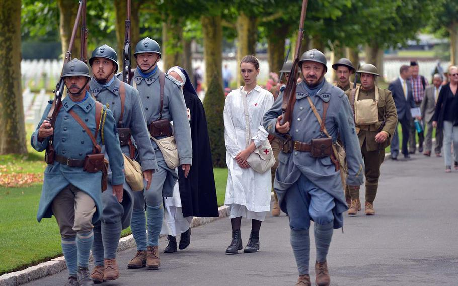 French re-enactors dressed in World War I-style uniforms march through Oise-Aisne American Cemetery at Seringes-et-Nesles, France, before the start of the ceremony marking the 100th anniversary of the World War I Oise-Aisne Offensive, Saturday, July 28, 2018.