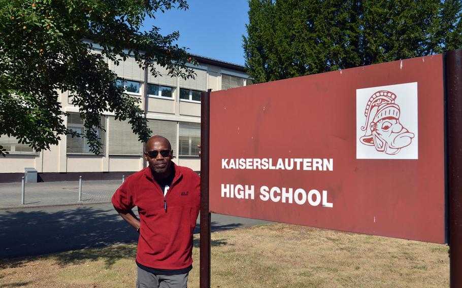 Kaiserslautern High School principal Barriett Smith stands next to the old school sign with its Raider mascot. When the school wanted to make minor changes to the Raider, the complaints from alumni were loud, Smith said. The Raider remained unchanged. Smith graduated from KHS in 1976.