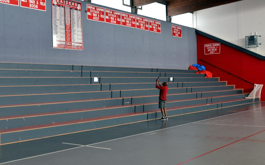 Kaiserslautern High School principal Barriett Smith takes a photo of Raiders track and field records that hang in the old KHS gym. The sign and the championship banners will hang in the new high school gym. Smith is a KHS alumnus, graduating in 1976.