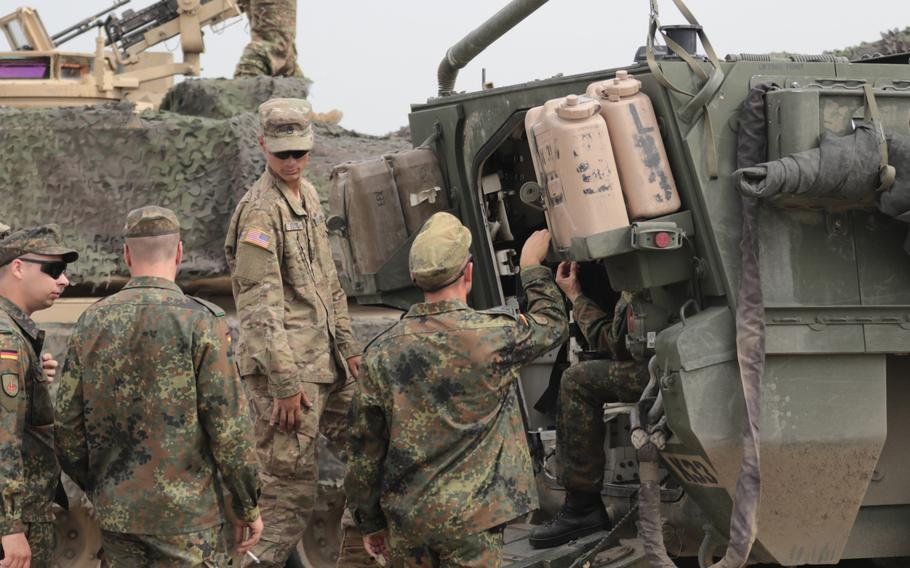 Staff Sgt. Keenan M. Kozak, a tank commander, listens to questions from German soldiers about the Stryker vehicle prior to the opening ceremonies of Noble Partner 18 at the Vaziani Training Area, Georgia on Aug 1, 2018.