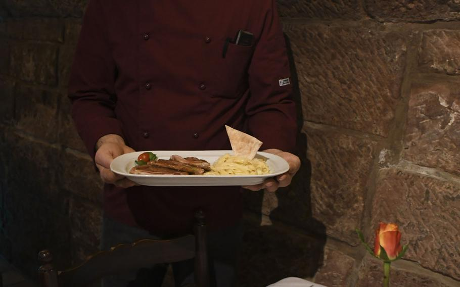 Skendo Shala, the chef of Ristorante Cardinale in Kaiserslautern, Germany, holds a plate of saltimbocca alla Romana, made of veal lined with prosciutto.