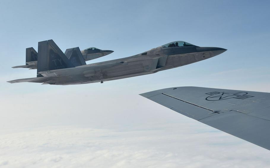 Two U.S. Air Force F-22 Raptors of the 325th Fighter Wing fly off the wing of a KC-135 Stratotanker of the 100th Air Refueling Wing after taking on fuel on their way to Norway, Wednesday, Aug. 15, 2018. Two Raptors were joined in the air by two Norwegian air force F-35s.