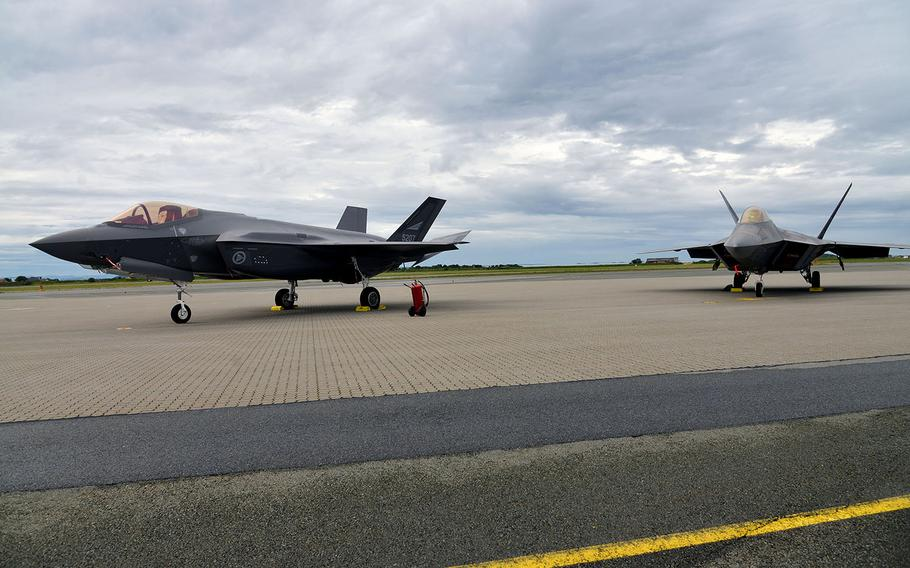 A Norwegian F-35 and a U.S. Air Force F-22 Raptor stand on the tarmac after landing at Orland Main Air Station, Norway, Wednesday, Aug. 15, 2018.