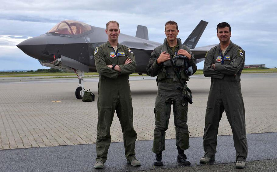 F-22 Raptor pilots Capt. Ian Gregoire, left, and Lt. Col. Matthew Tromans flank Norwegian F-35 pilot Maj. Morten Hanche as they pose for photographers after landing their fifth-generation aircraft at Orland Main Air Station, Norway, Wednesday, August 15, 2018.