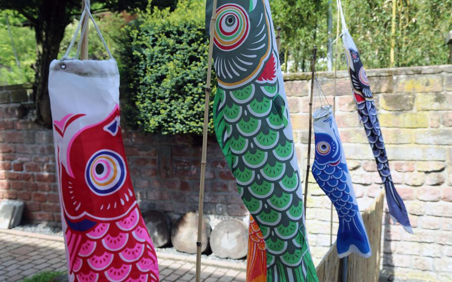 Banners colored to represent koi flutter in the wind outside the Japanese Garden in Kaserslautern, Germany.