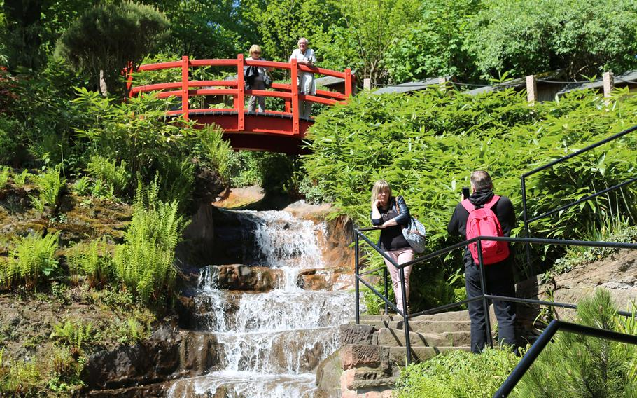 Tourists take photographs in front of a waterfall in the Japanese Garden in Kaiserslautern, Germany. Opened in 2000, the garden has become a place of peace and meditation for locals and members of the military community.