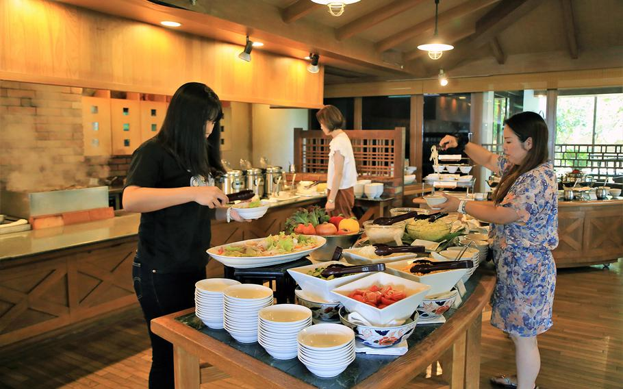 Diners at Makan Makan try the cold food station, which includes a salad bar and a make-your-own noodle bowl bar.
