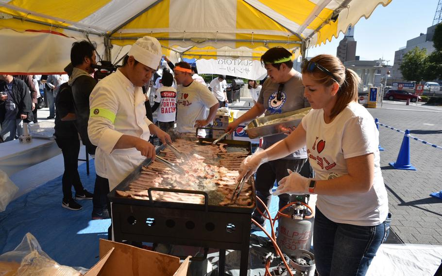 Festival staff fry some of the 40,000 strips of bacon given away at the Japan Bacon Festival in Kofu, Japan, on Nov. 3, 2017.
