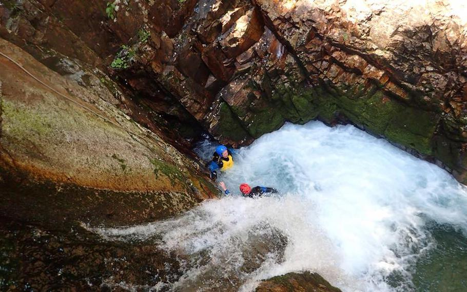 Canyoners take a break in the pool below a 20-foot waterfall. The water is deep enough to dive into head first.