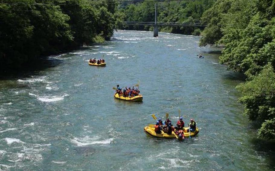 Canyons also offers whitewater rafting excursions throughout Japan. In this photo, three groups of rafters from Yokosuka on an MWR trip in June float down the Tone River among the mountains in Gunma Prefecture.