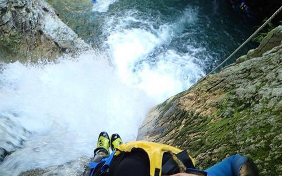 Stars and Stripes reporter Caitlin Doornbos rappels down a 20-meter waterfall before dropping into the water on a Canyons tour. Canyoning encompasses many forms of traveling through canyons, including climbing, swimming, rappelling and jumping. (Courtesy of Canyons)