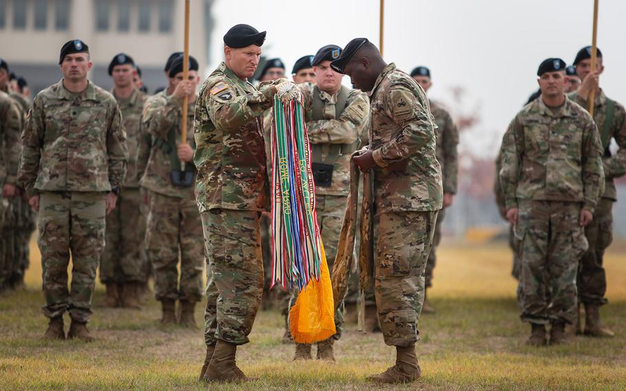 Col. Marc Cloutier and Command Sgt. Maj. Michael Oliver of the 3rd Armored Brigade Combat Team, 1st Armored Division, unfurl their units colors during a transfer of authority ceremony at Camp Humphreys, South Korea, Monday, Oct. 22, 2018.