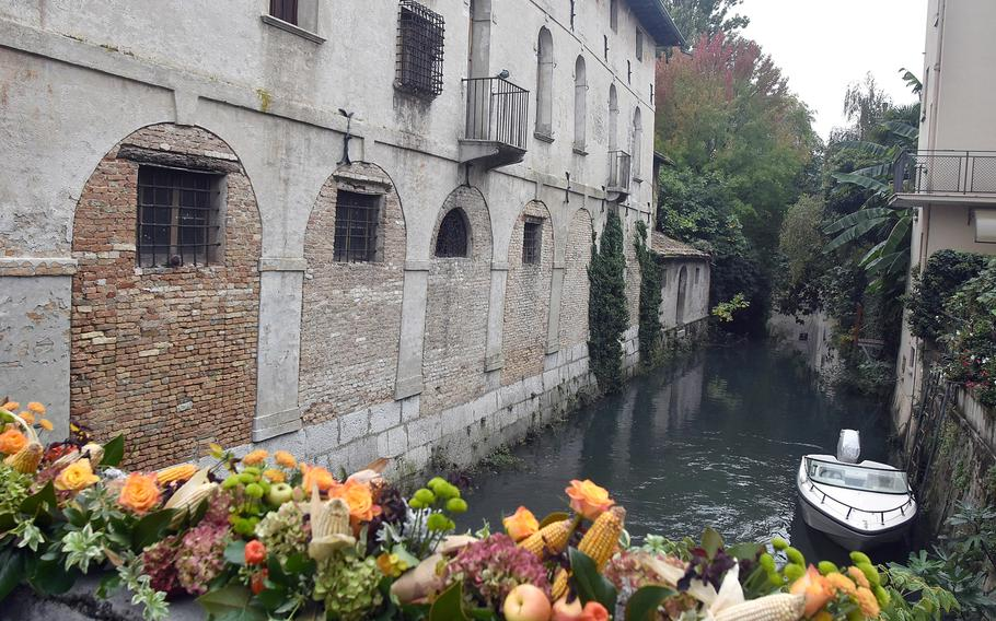 One of several parts of the Lemene river winds its way through downtown Portogruaro, Italy, under a bridge festooned in fall colors.