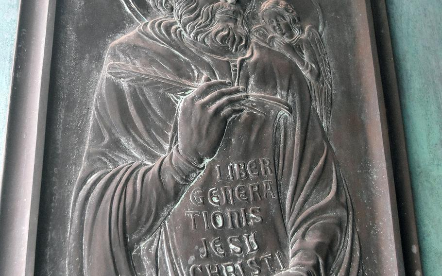 This plaque decorates a door of the Chiesa di San Giovanni in Portogruaro, Italy. The church is located on one of the pedestrian areas in the historic city center.