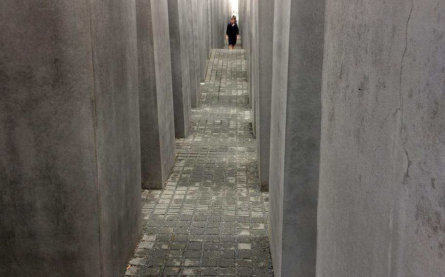 Visitors walk through the Field of Stelae at the Memorial to the Murdered Jews of Europe in Berlin, Germany. The 2,711 stelae are of the same width and length, but of different heights, ranging from about eight inches to over 15 feet.