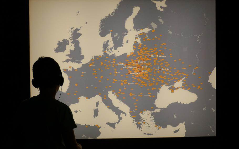 A boy listens to the description of the ''Room of Sites,'' while looking at a map that marks sites around Europe where Jews were persecuted and murdered.