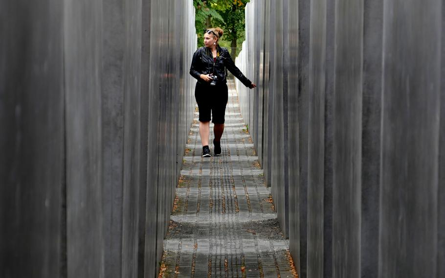 A visitor walks through the Field of Stelae at the Memorial to the Murdered Jews of Europe in Berlin, Germany. The 2,711 stelae are of the same width and length, but of different heights ranging from about eight inches to over 15 feet.