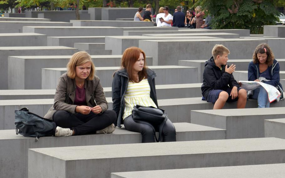 Visitors sit on stelae of the Memorial to the Murdered Jews of Europe in Berlin, Germany. While sitting is frowned upon but allowed, standing and jumping on the stelae is not.