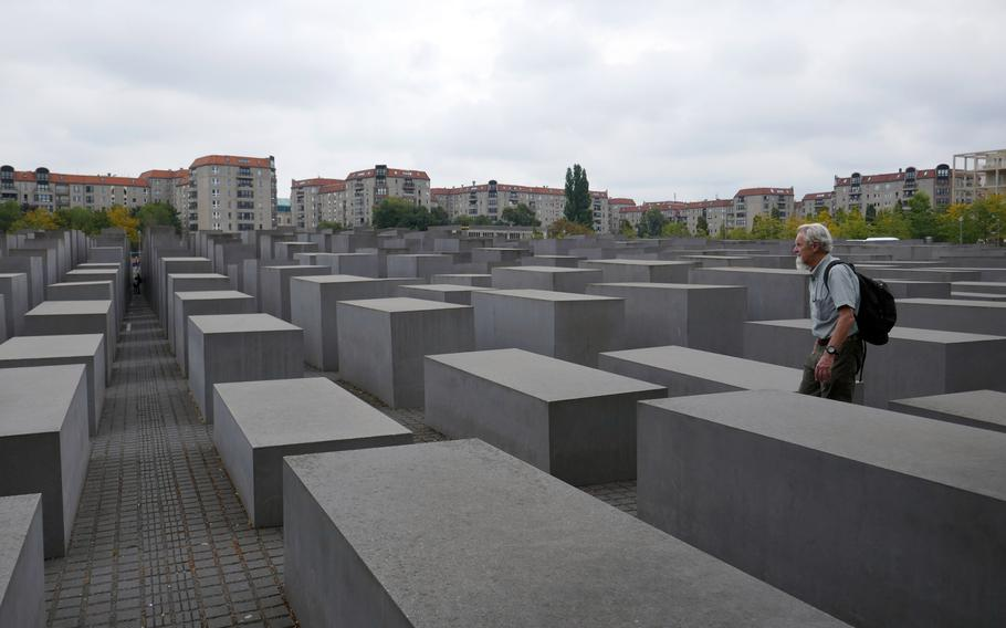Visitors walk through the Field of Stelae at the Memorial to the Murdered Jews of Europe in Berlin, Germany. The 2,711 stelae are 7 feet, 10 inches long and 3 feet 1 inch wide, with heights ranging from about eight inches to over 15 feet.