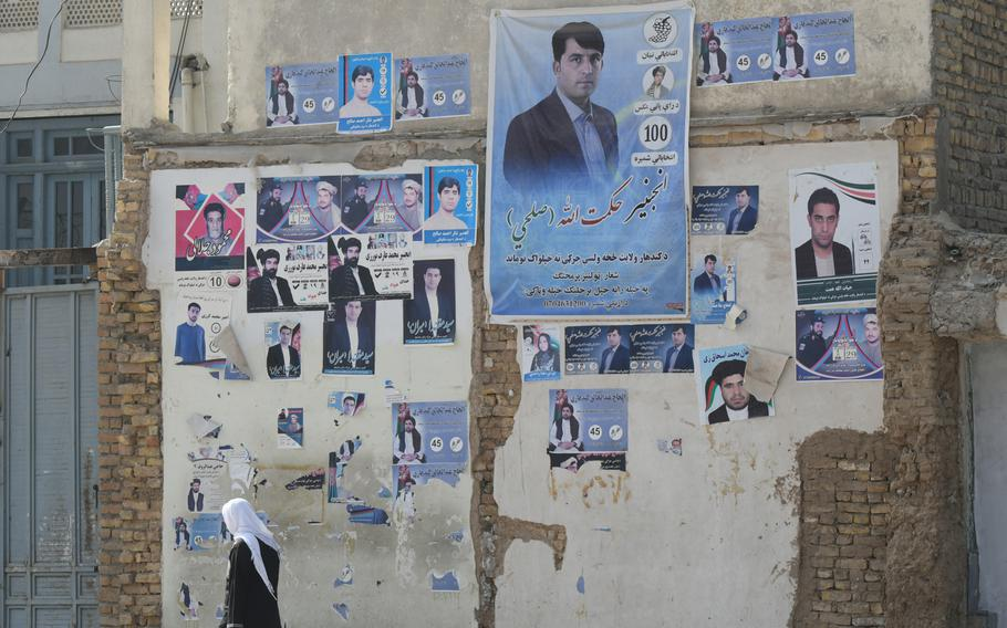 A man walks past campaign posters in Kandahar, Afghanistan, on Saturday, Oct. 27, 2018, the day the province voted in delayed parliamentary elections.
