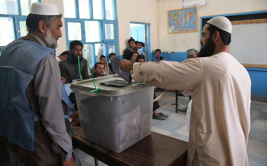 A voter in Kandahar, Afghanistan, casts his ballot in delayed parliamentary elections as election observers watch on Saturday, Oct. 27, 2018.