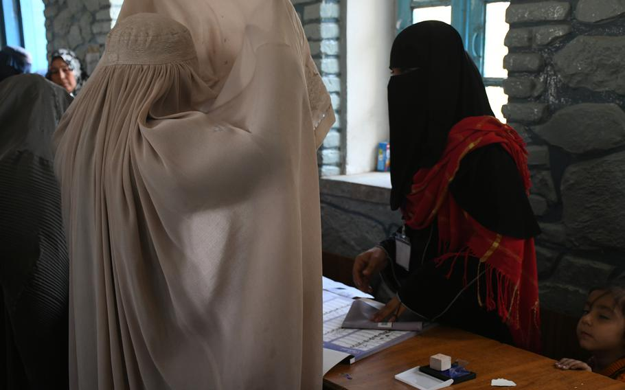 A woman lifts her burqa and shows her face to an election official so she can be identified to vote in parliamentary elections on Saturday, Oct. 27, 2018.