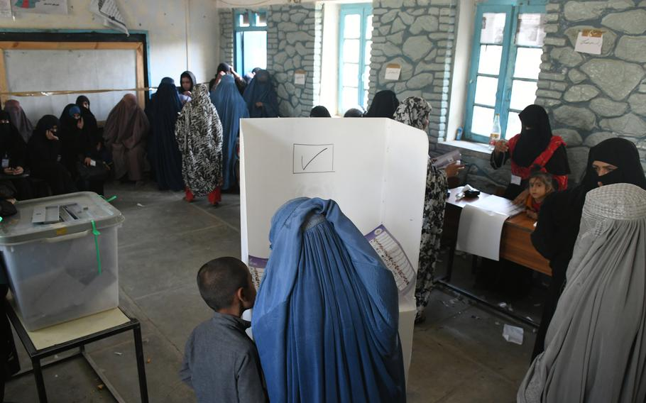 A boy accompanies his mother at a polling both in Kandahar, Afghanistan, on Saturday, Oct. 27, 2018.