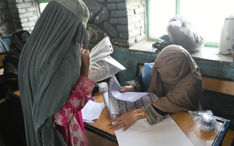 A woman in Kandahar, Afghanistan, receives her ballot to vote in parliamentary elections on Saturday, Oct. 27, 2018.