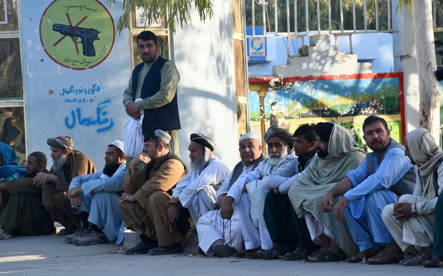 Men wait to vote at a polling center in Kandahar's Aino Maina neighborhood. The center opened late on Saturday, Oct. 27, 2018, because staff had difficulties using the biometric identification machines.