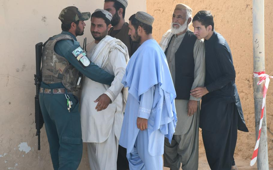A police officer searches voters at a polling center in Kandahar?s Dorahi neighborhood on Saturday, Oct. 27, 2018.