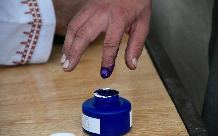 A man dips his finger into ink at a polling center in Kandahar, Afghanistan, on Saturday, Oct. 27, 2018, to signify he has voted in parliamentary elections.