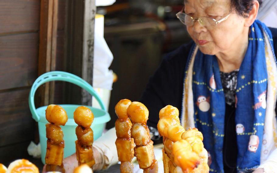 A food stand employee tends to the sweet miso-grazed dekomawashi roasting on the grill near Iya-no-Kazurabashi.