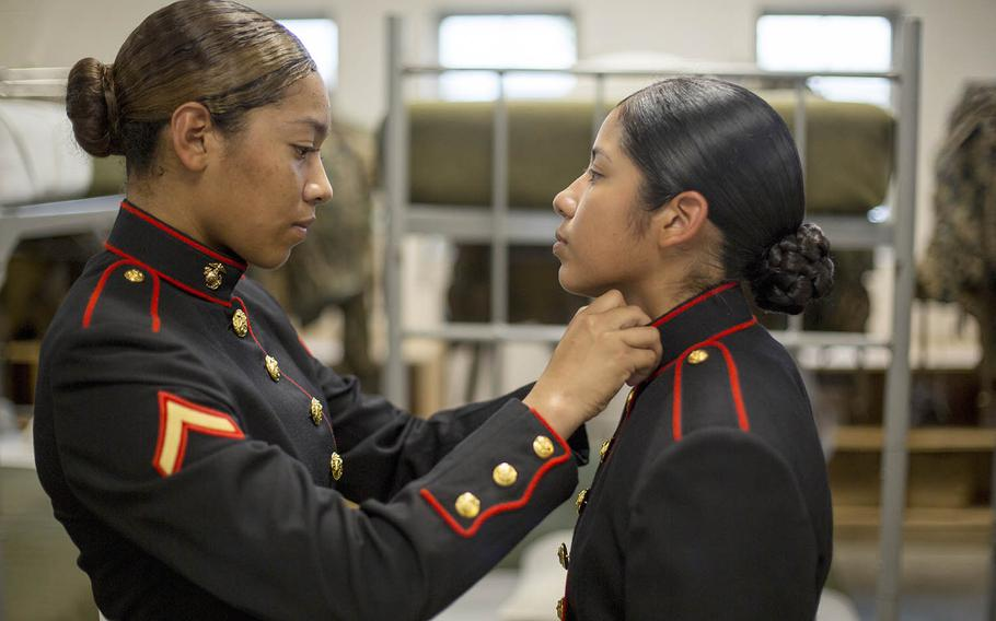 Pfc. Kathy Espinoza, of New York, N.Y., inspects the uniform of Pvt. Arella Aleman, of Dallas, at Marine Corps Recruit Depot Parris Island, S.C., Nov. 9, 2018.